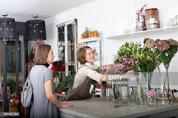 florist preparing a bouquet with a customer