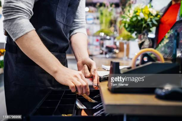 florist putting cash in his register - cash register stock pictures, royalty-free photos & images