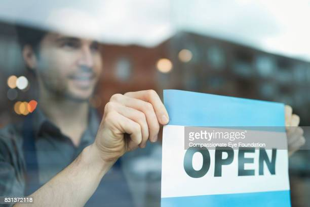 florist putting up open sign in flower shop window - open for business stock pictures, royalty-free photos & images