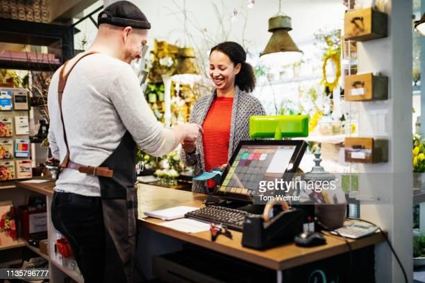 florist serving customer at cash register - consumismo - fotografias e filmes do acervo