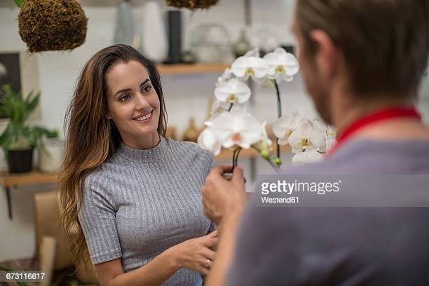 Florist showing orchids to customer