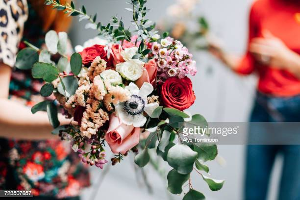florist student holding bunch of cut flowers at flower arranging workshop - arranging stock pictures, royalty-free photos & images