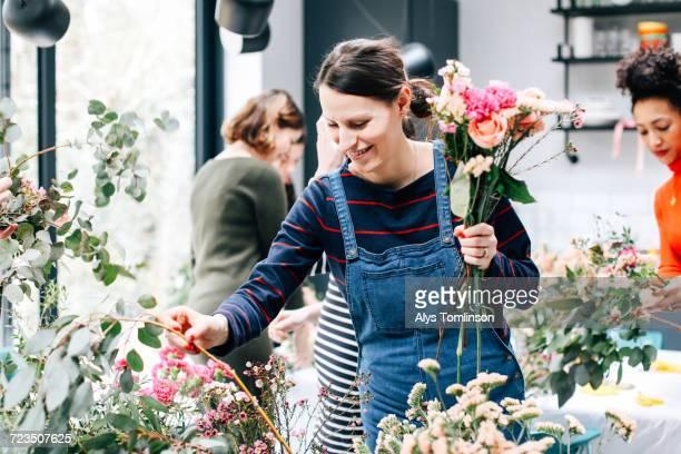 Florist student selecting cut flowers at flower arranging workshop
