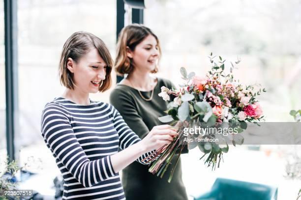 Florist students arranging bouquets at flower arranging workshop