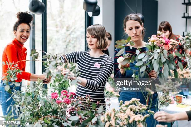 florist students selecting cut flowers at flower arranging workshop - composizione di fiori foto e immagini stock