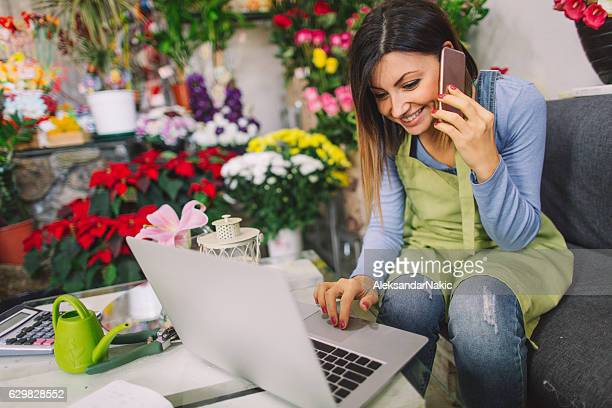 florist taking orders on the phone - happy merchant stock pictures, royalty-free photos & images
