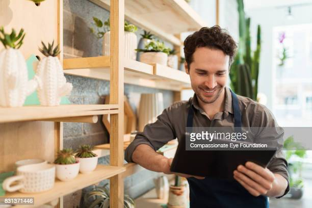 florist using digital tablet in flower shop - entrepreneur - fotografias e filmes do acervo