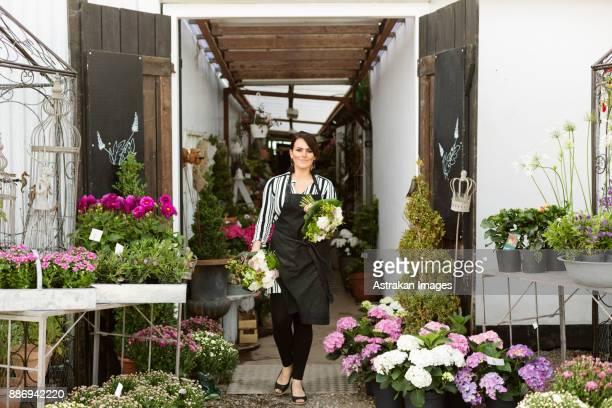 Florist walking with bouquets in flower shop