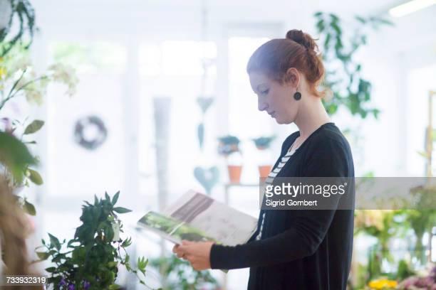 florist working in shop - sigrid gombert fotografías e imágenes de stock