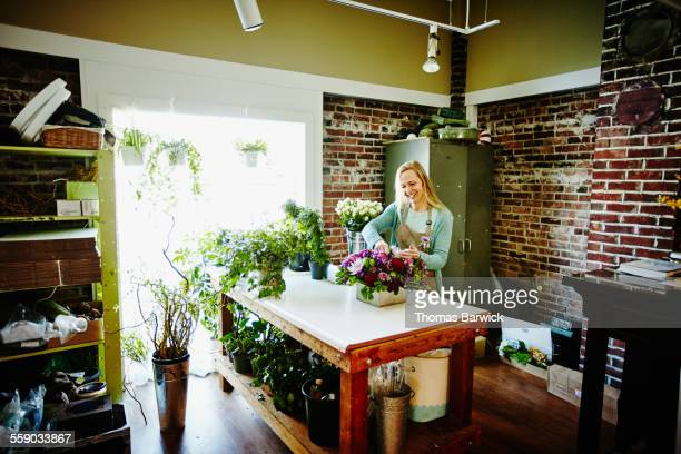 Florist working on arrangement at workbench