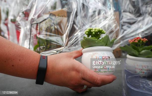 A florists shows a small pot with a plant and the words 'Happy Mothers Day' written on it in a flower shop in MerbesLeChateau Belgium on May 9 2020...