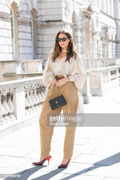 Florrie Thomas wears a Kurt Geiger bag, Victoria Beckham shoes, Rag and Bone sunglasses, Flow belt, trousers and shirt on September 13, 2019 in...