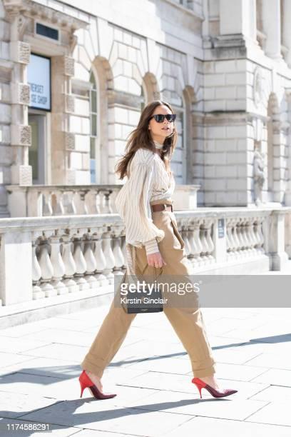 Florrie Thomas wears a Kurt Geiger bag, Victoria Beckham shoes, Rag and Bone sunglasses, Flow belt, trousers and shirt on September 13, 2019 in...