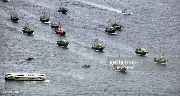 Flotilla of fishing boat bearing both the Chinese and Hong Kong flags sails past a Star Ferry in Hong Kong on July 1, 2012 during celebrations to...