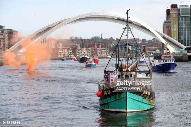 A flotilla of fishing vessels passes under the Millennium Bridge in Newcastle northeast England on April 8 during a protest against the Brexit...
