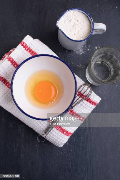 Flour, eggs, milk and water on the table