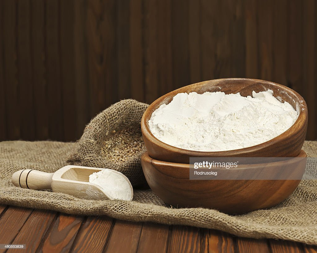 Farinha na Tigela de madeira e trigo em saco de Aniagem de Cânhamo. : Foto de stock