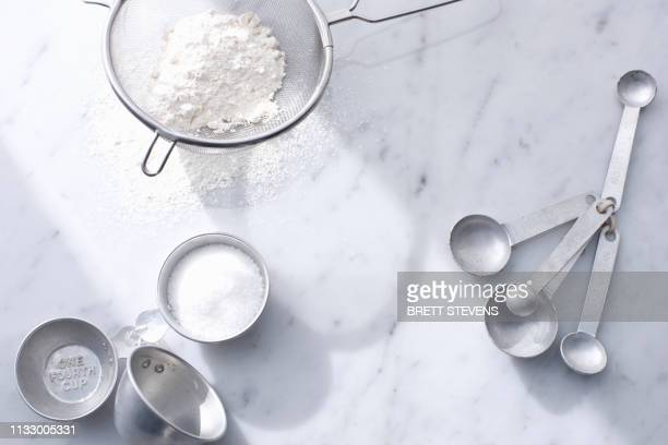 flour with measuring cups and spoons - kitchen utensil stock pictures, royalty-free photos & images