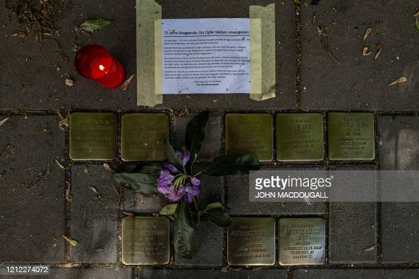 A flower and a lit candle are placed next to Stolpersteine small brass plaques commemorating Holocaust victims outside their former homes in Berlin...