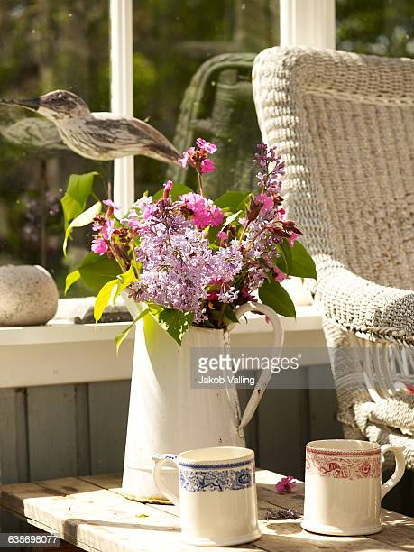 Flower arrangement in rustic jug on conservatory side table