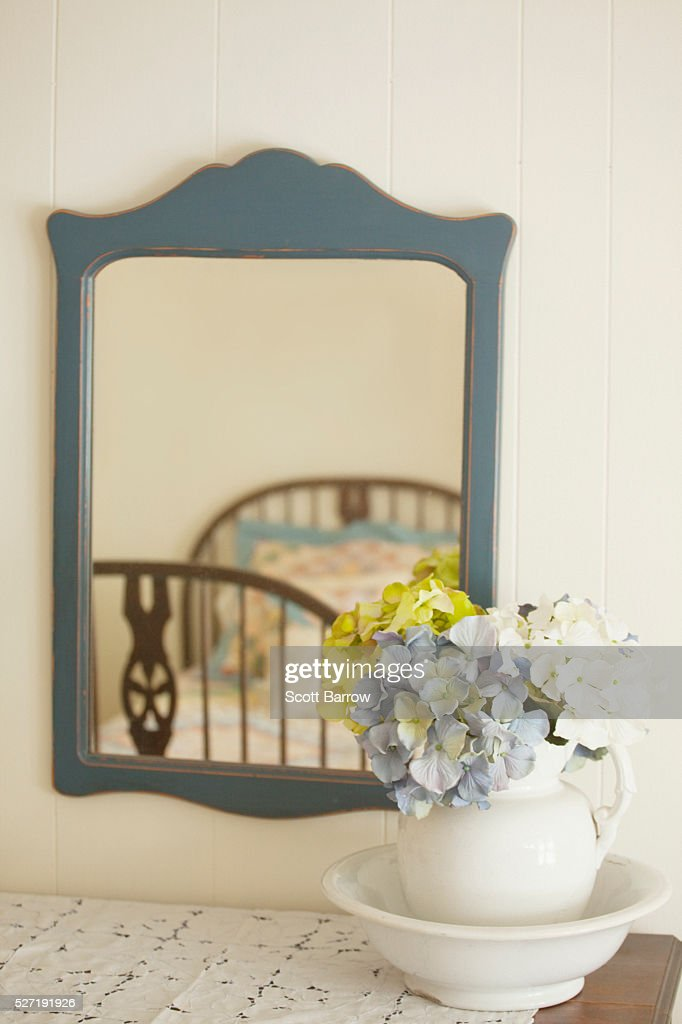 Flower arrangement on dresser beside mirror : ストックフォト