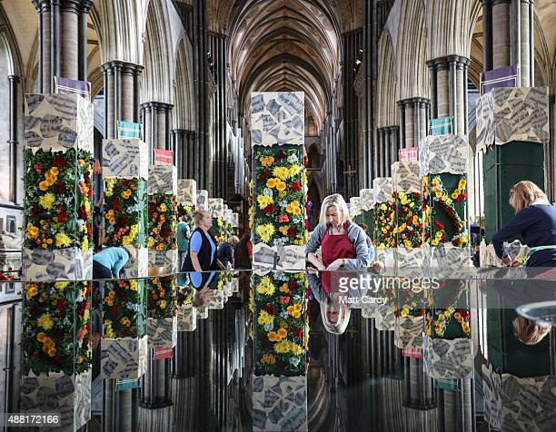 Flower arrangers are reflected in the font as they work on Salisbury Cathedral's flower festival themed around the Magna Carta at Salisbury Cathedral...