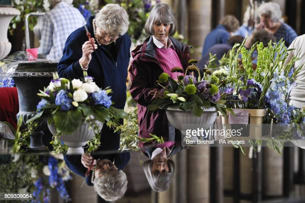 Flower arrangers are reflected in the font at Salisbury Cathedral as they create its spectacular Flower Festival which opens to the public on Tuesday...
