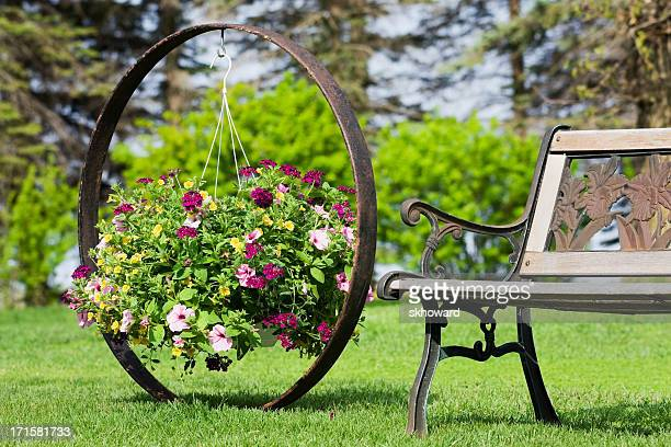 flower basket hanging on wagon wheel by garden bench - hanging basket stock pictures, royalty-free photos & images