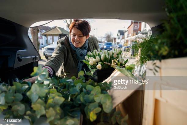 flower delivery business - femalefocuscollection stock pictures, royalty-free photos & images