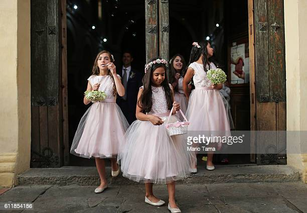 Flower girl blows bubbles as the wedding party departs a historic church following the marriage ceremony October 1, 2016 in Bogota, Colombia....