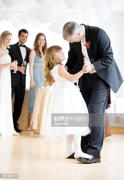 Flower girl dancing on Fathers feet at wedding