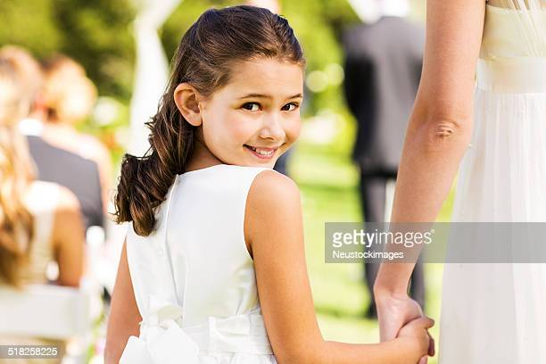 Flower Girl Holding Bride's Hand While Looking Over Shoulder