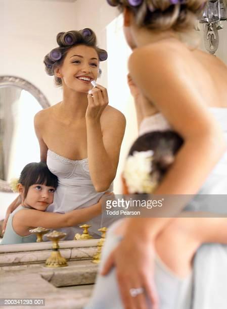 Flower girl (3-5) hugging bride as she applies lipstick in mirror