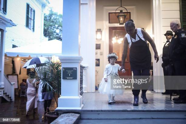 A flower girl is escorted toward the wedding of Victoria Yu and Nicholas Persac at the historic Degas House former home of French Impressionist...