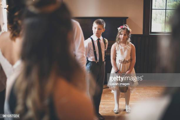 flower girl with pageboy looking at bride during wedding ceremony - pageboy stock pictures, royalty-free photos & images