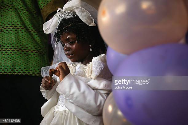 A flower girls eats at a wedding reception on January 24 2015 in Monrovia Liberia The bride and groom had waited until the worst of the Ebola...