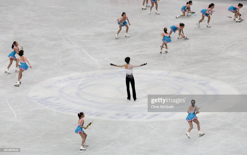 Flower girls rush to clear the ice as Yuzuru Hanyu of Japan salutes the crowd after finishing his routine in the Men's Free Skating during ISU World Figure Skating Championships at Saitama Super Arena on March 28, 2014 in Saitama, Japan.