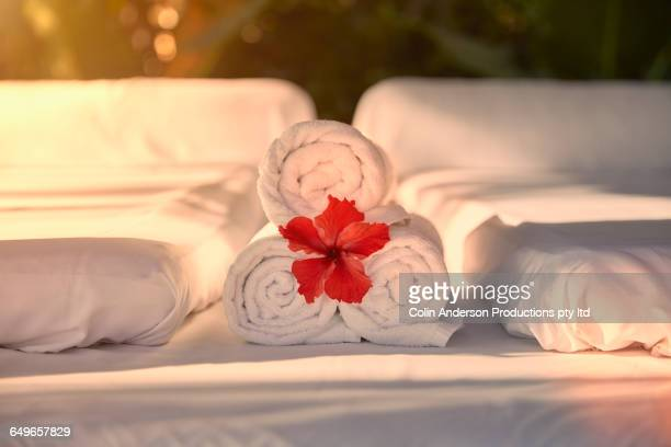 Flower in towel rolls on massage table