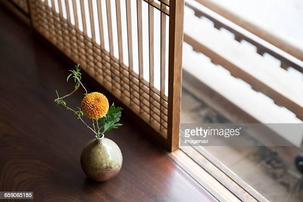 Flower in vase on wooden porch