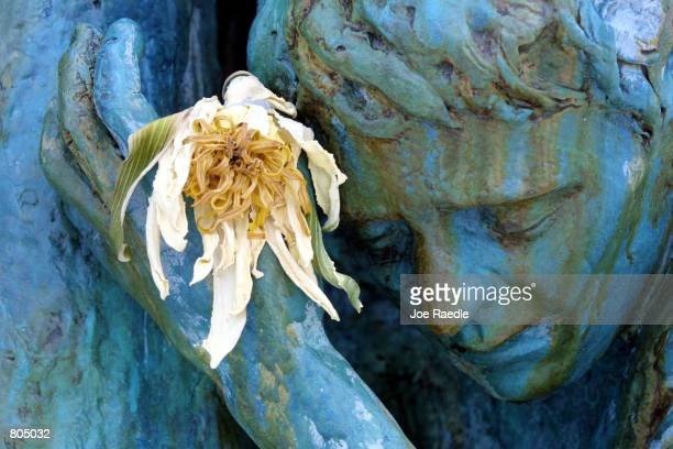 A flower is placed into the hand of a statue by artist Kenneth Treister which is part of a sculpture depicting thousands of victims crawling into an...