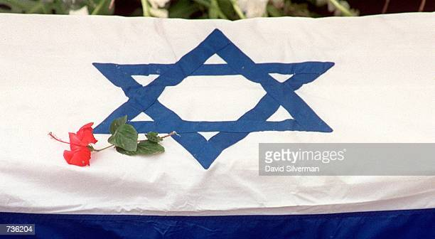Flower is placed on the flag-draped coffin of Leah Rabin, wife of assassinated former Prime Minister Yitzhak Rabin, during a ceremony November 15,...