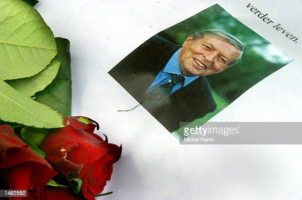 A flower lies next to a portrait of Prince Claus of the Netherlands husband to Dutch Queen Beatrix with the text 'Living On' written above the...