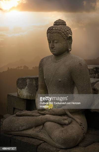 Flower offering and buddha, The Buddhist Temple of Borobudur, Java, Indonesia