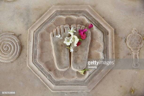 Flower offering on Krishna's lotus feet engraved on the floor in Kusum Sarovar India