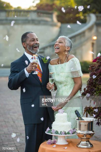 Flower petals falling on Black newlyweds