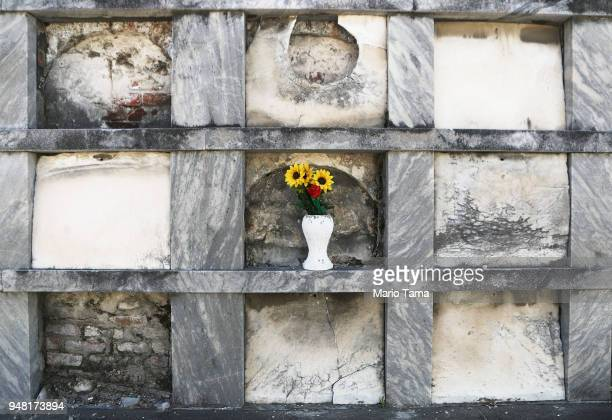 A flower pot stands amidst above ground tombs in St Roch Cemetery on April 16 2018 in New Orleans Louisiana New Orleans originally founded by the...