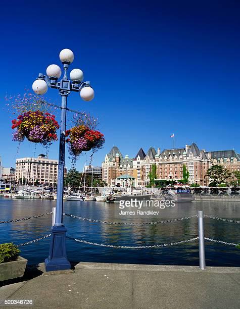 flower pots hanging on street light - カナダ ビクトリア市 ストックフォトと画像