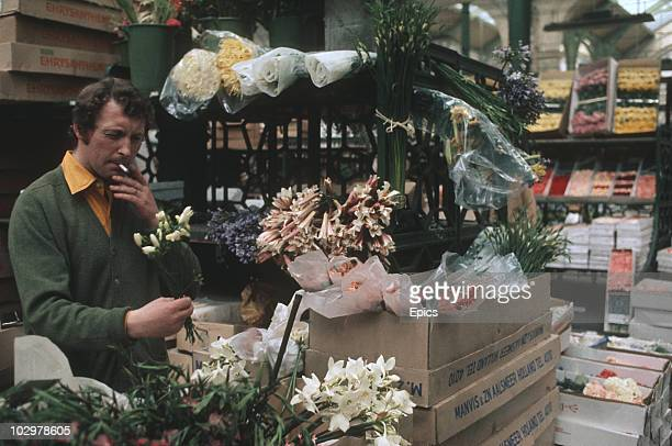 A flower seller takes a puff on a cigarette whilst working his stall in London's Covent Garden Market circa 1970
