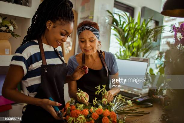 flower shop workers - florist stock pictures, royalty-free photos & images