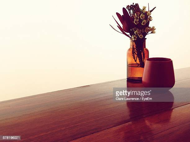 Flower Vase And Container On Wooden Table Against White Wall